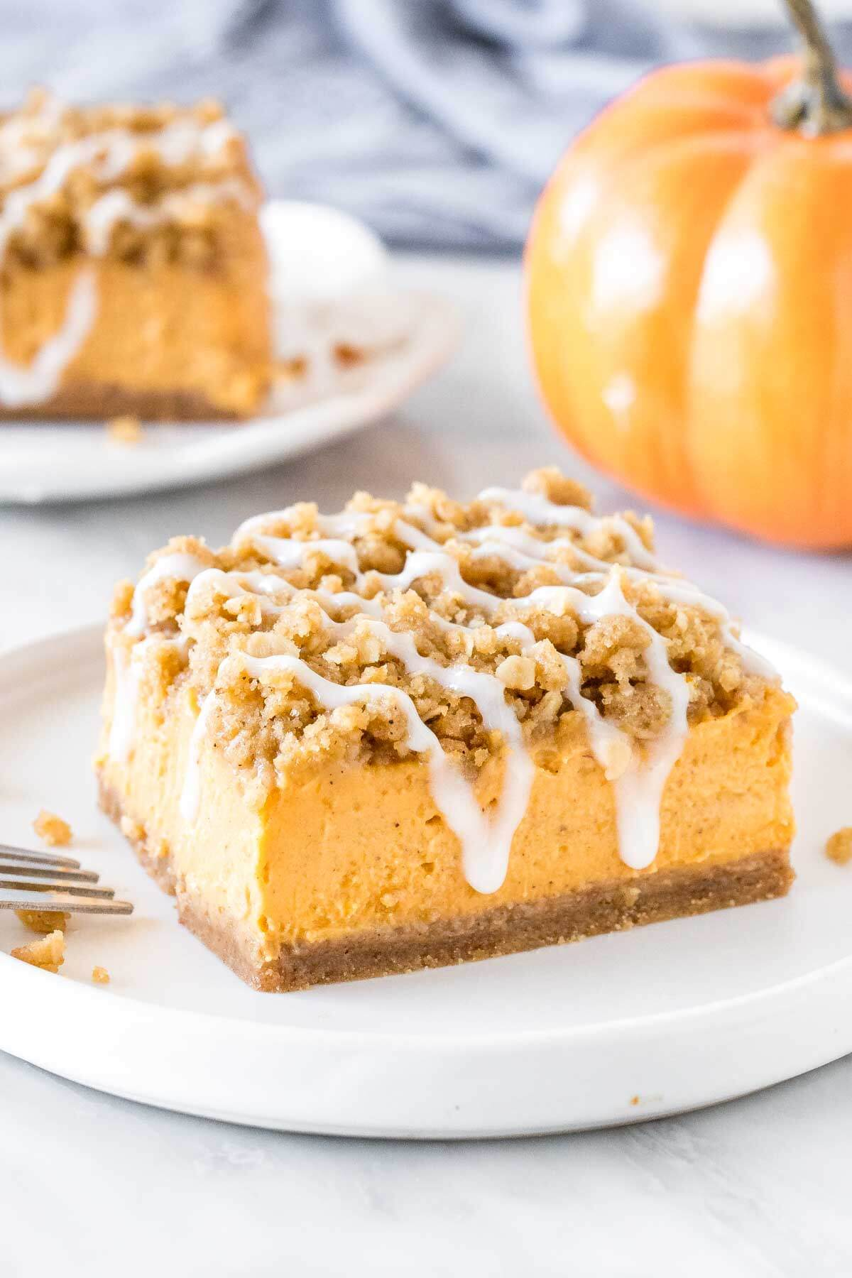 Slice of pumpkin streusel bars on a plate with a second piece in the background.