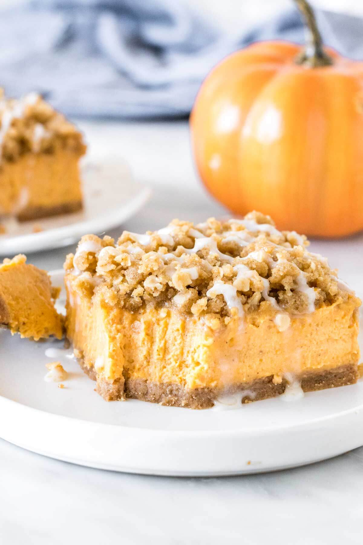 Slice of pumpkin cheesecake bars with oatmeal topping on a plate.