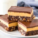Plate of peanut butter nanaimo bars with a glass of milk