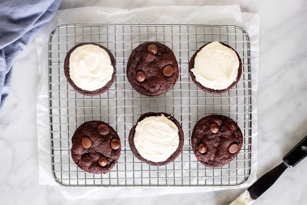 Chocolate cookies on a wire cooling rack with vanilla frosting.