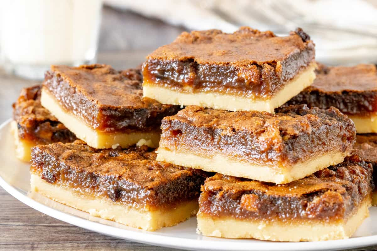 Plate of butter tart squares, stacked on top of each other.