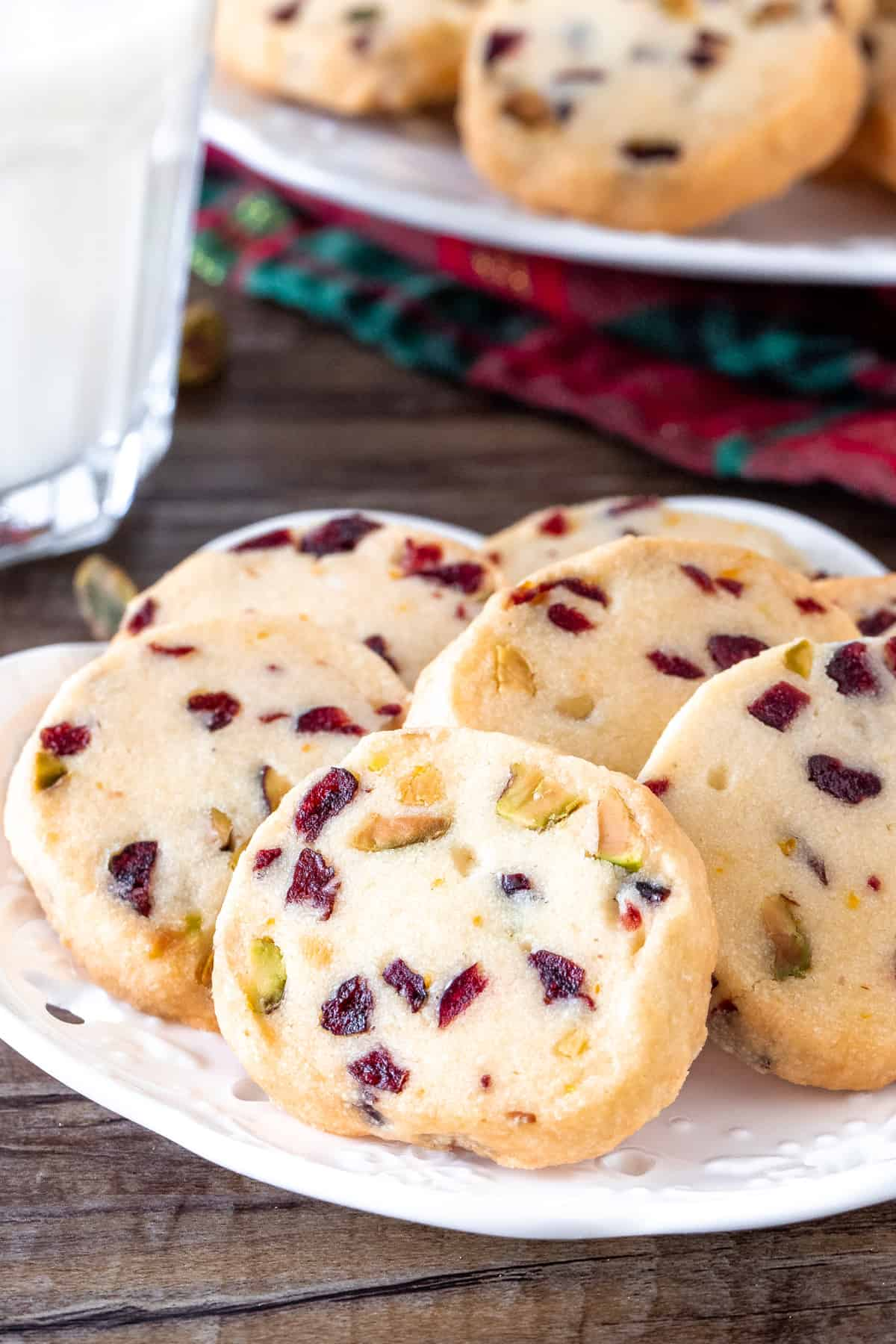 Cranberry orange shortbread on a plate with a glass of milk.