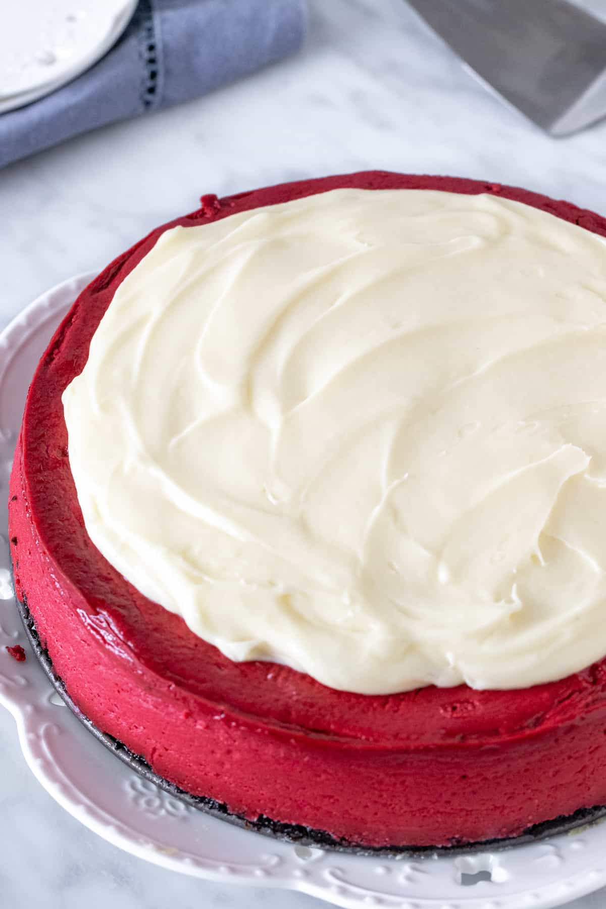 Red Velvet cheesecake with cream cheese topping on a plate.