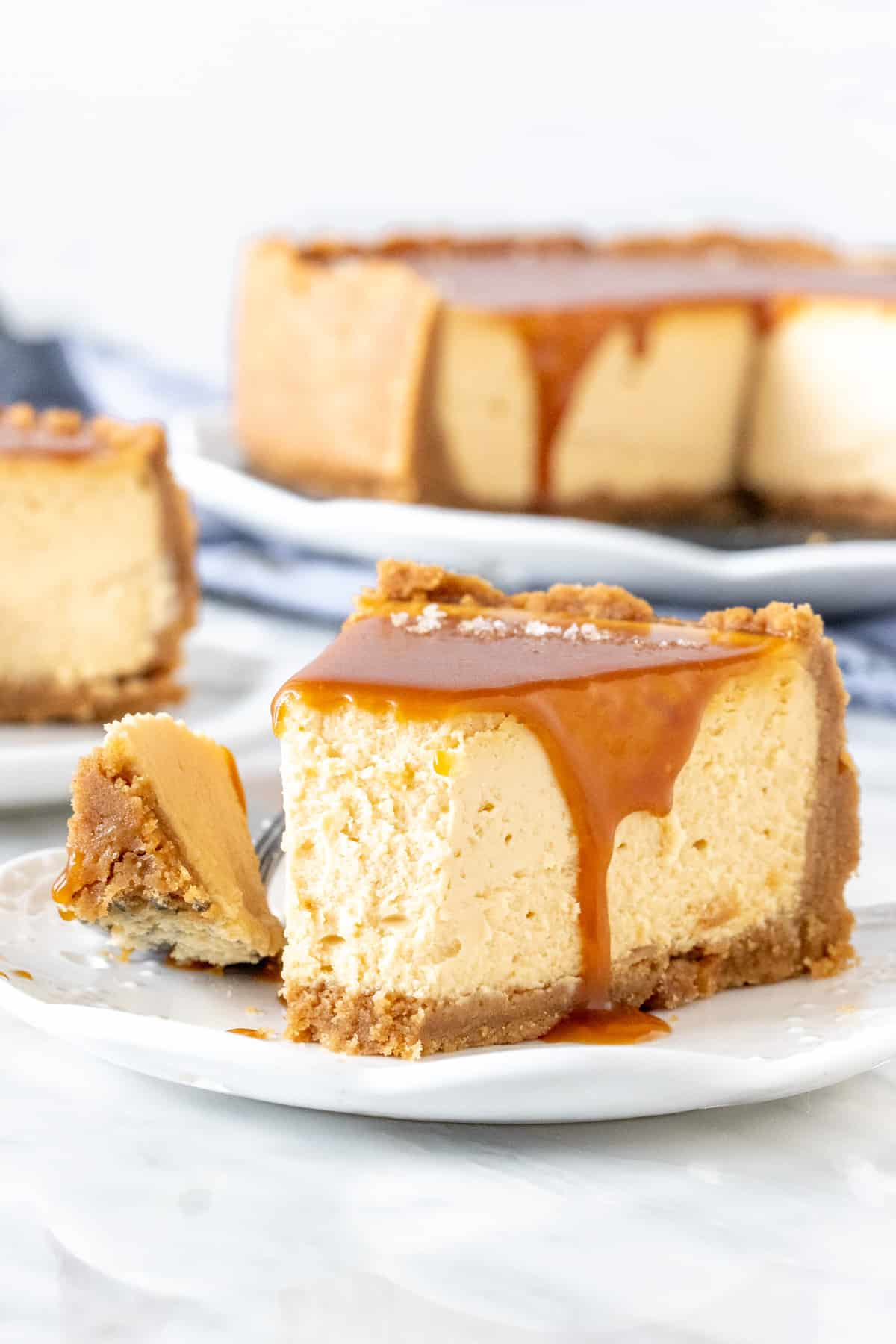 Slice of caramel cheesecake with a bite taken out of it.