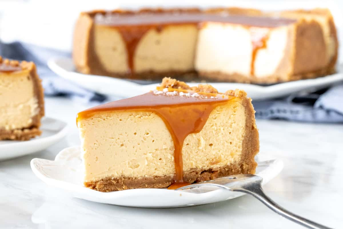 Slice of cheesecake with caramel running down the sides.