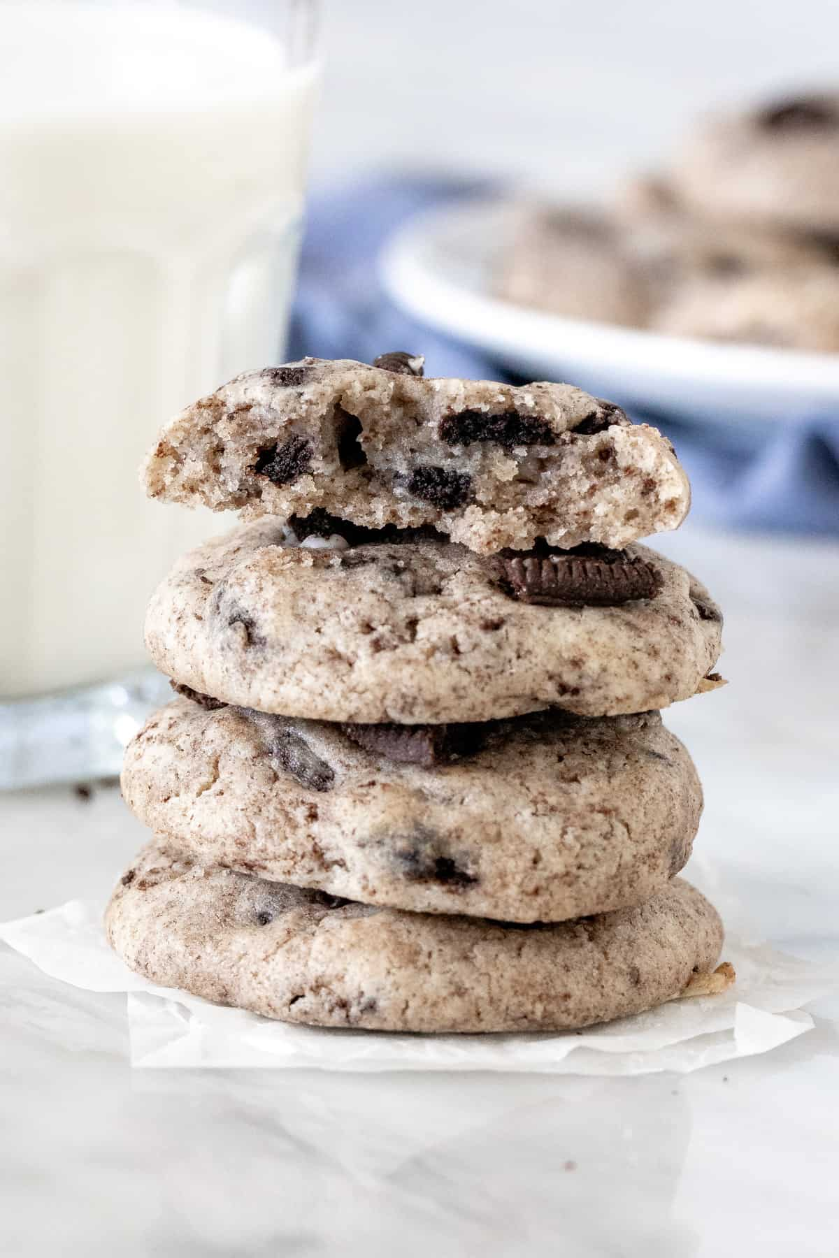 Stack of Oreo cheesecake cookies with the top cookie broken in half.
