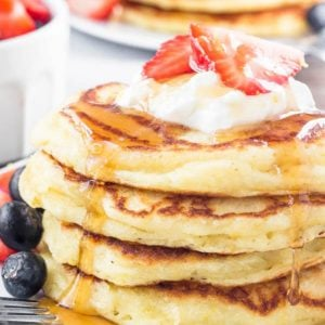 Stack of pancakes with whipped cream and syrup.