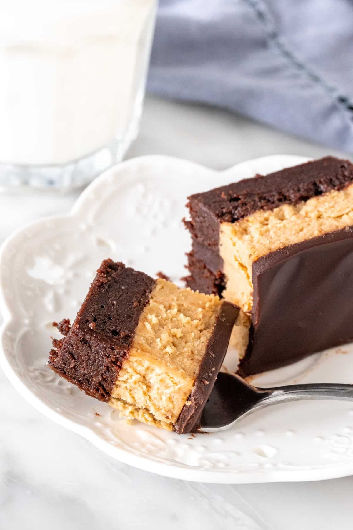 A bite of a peanut butter cheesecake brownie on a plate.