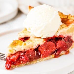 Slice of strawberry pie with a scoop of ice cream.