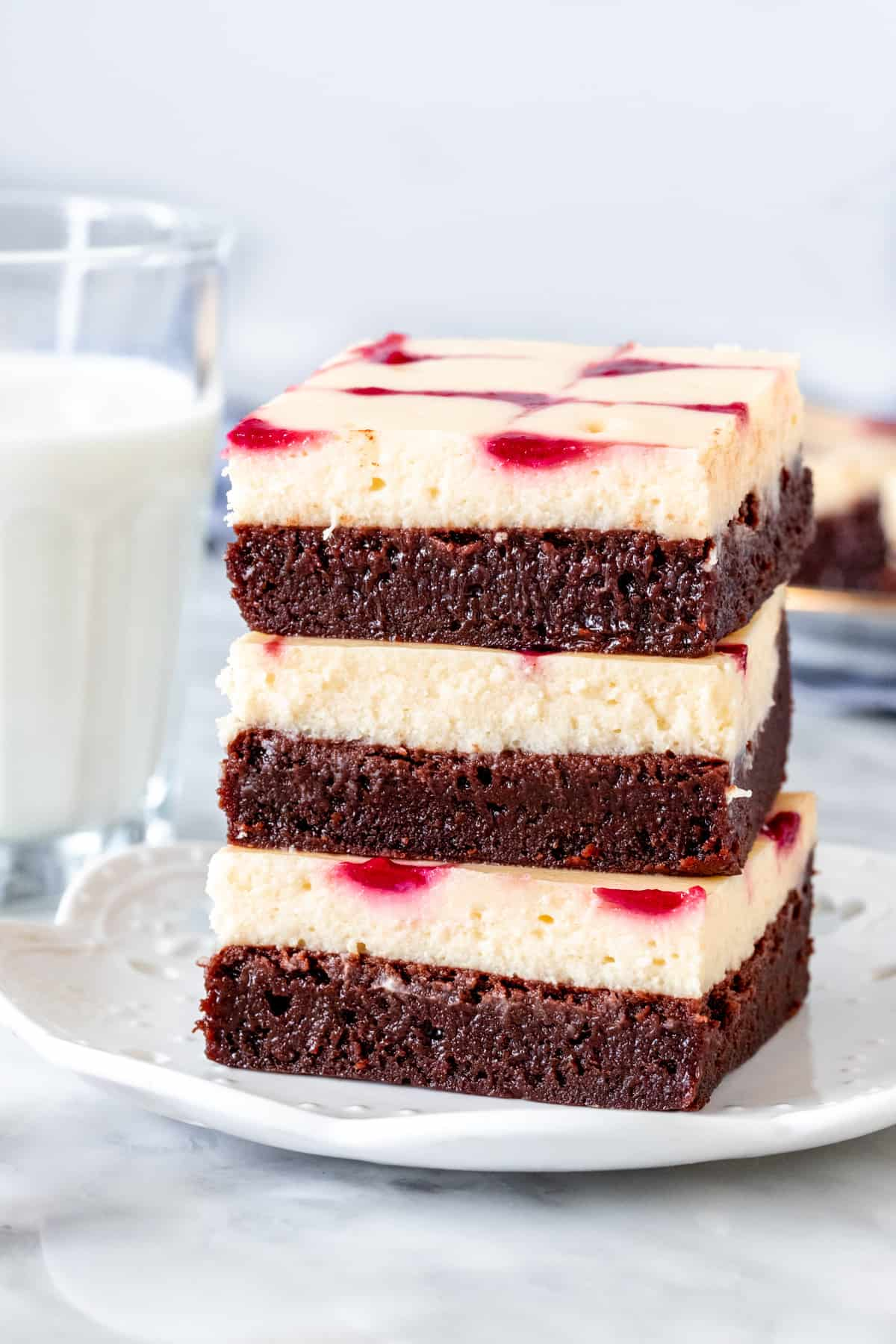Stack of three raspberry cheesecake brownies on a plate.