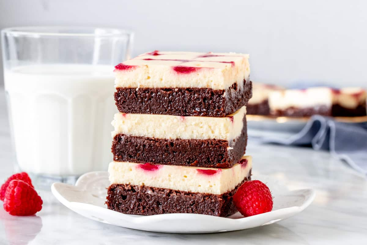 Stack of layered cream cheese brownies with a raspberry swirl on a plate.