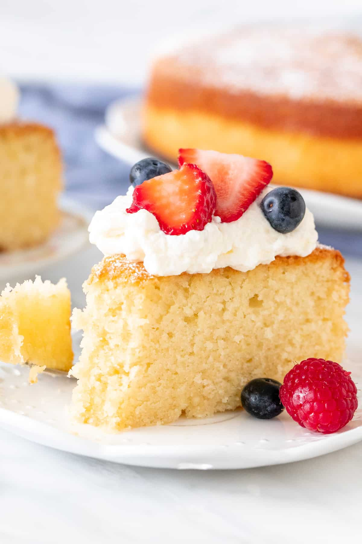 Slice of lemon olive oil cake with whipped cream and berries on top.