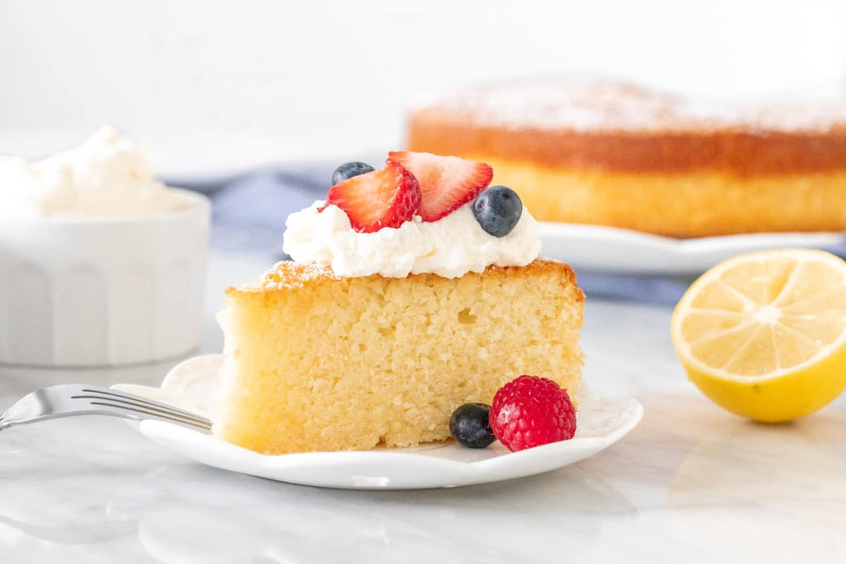 Slice of plain cake with berries and cream on top.