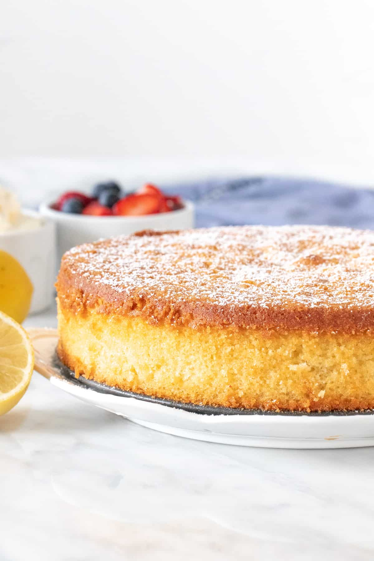9-inch round lemon cake with powdered sugar sprinkled on top.