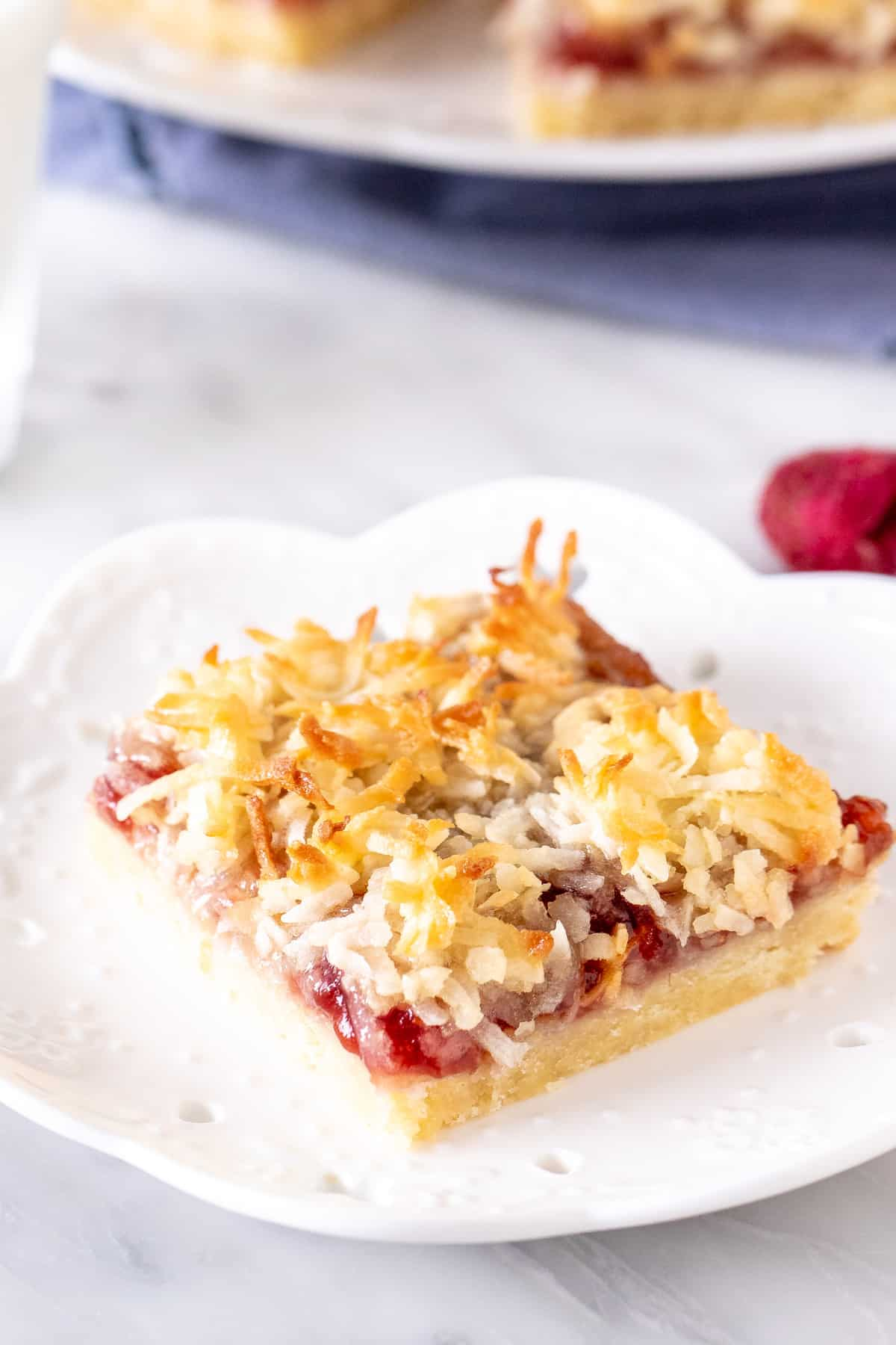 Raspberry coconut slice on a plate.