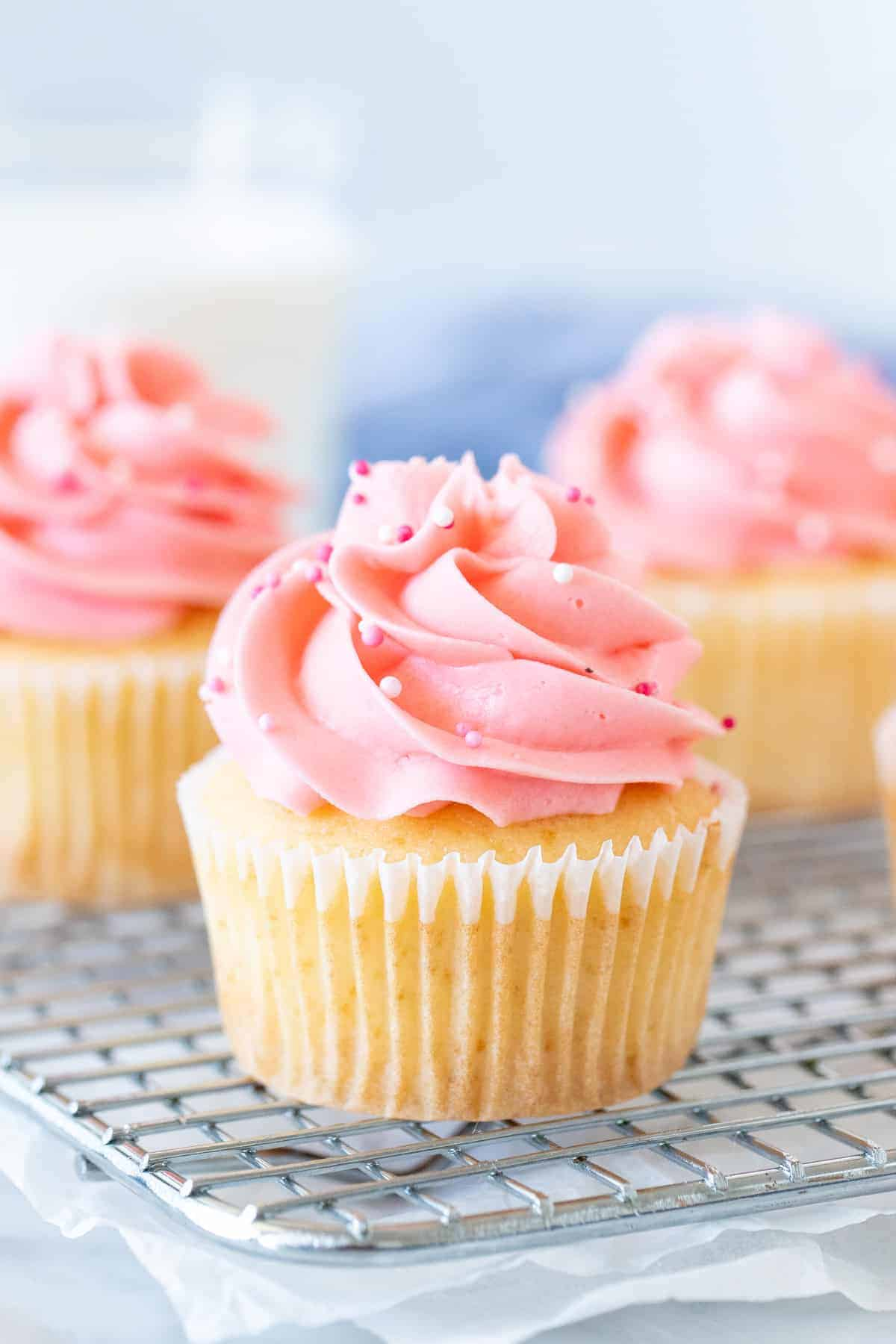 Vanilla cupcakes with pink frosting on cooling rack.