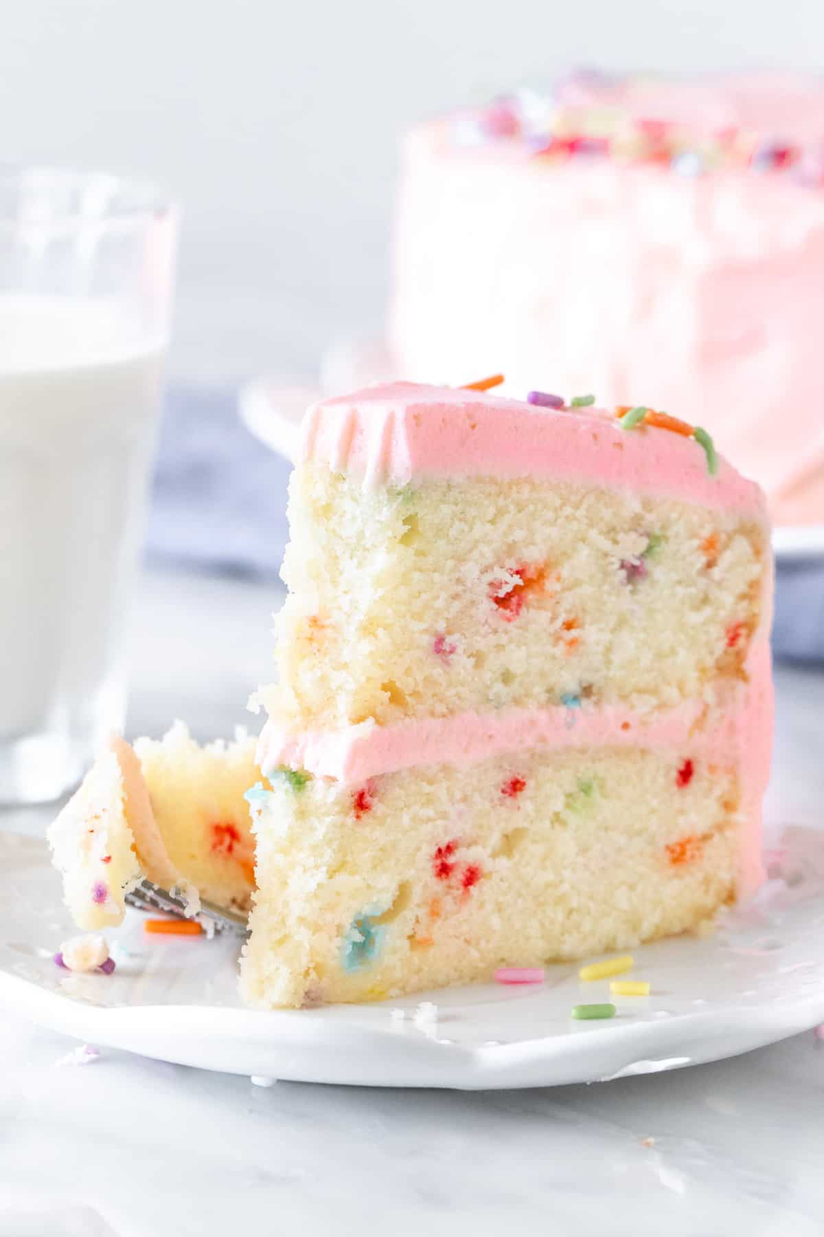 Slice of funfetti cake with pink frosting.