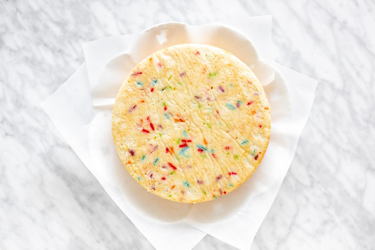 A layer of funfetti cake on a plate.