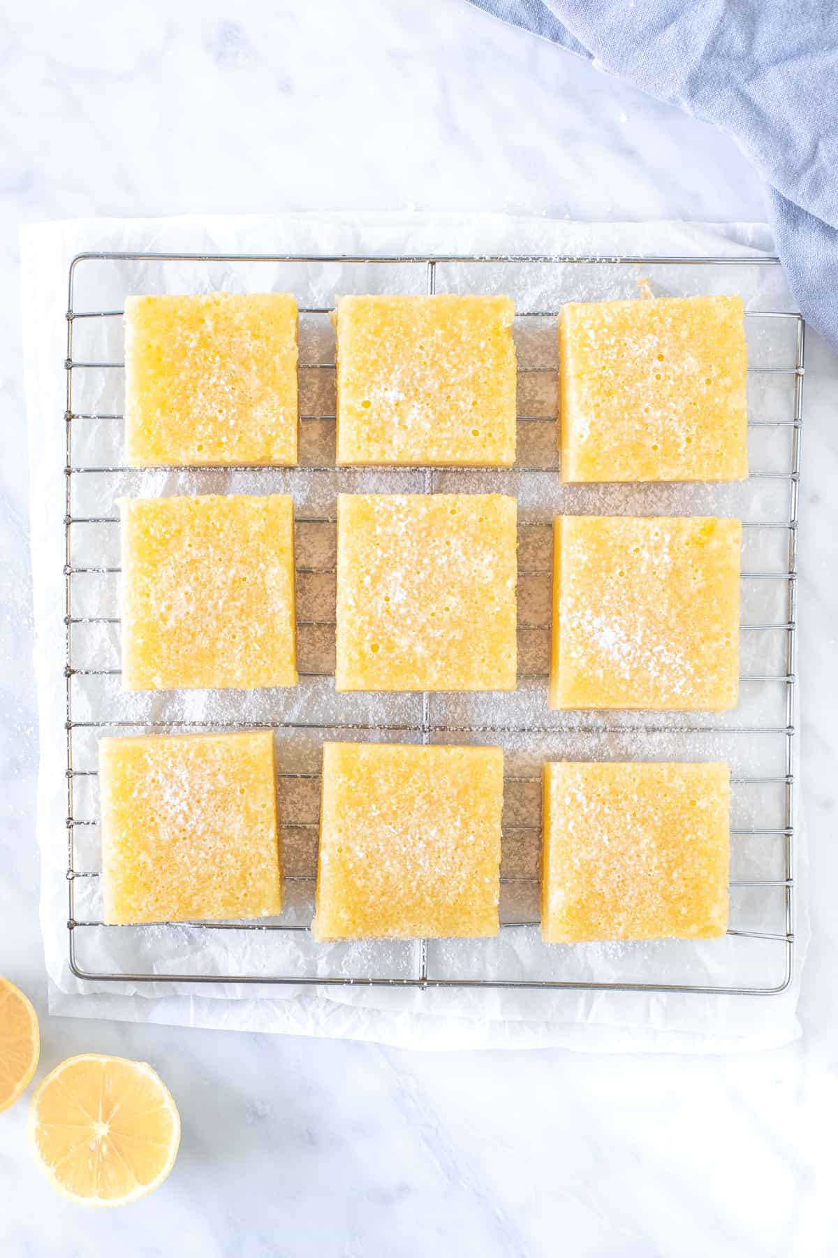 9 lemon bars on a cooling rack sprinkled with powdered sugar.