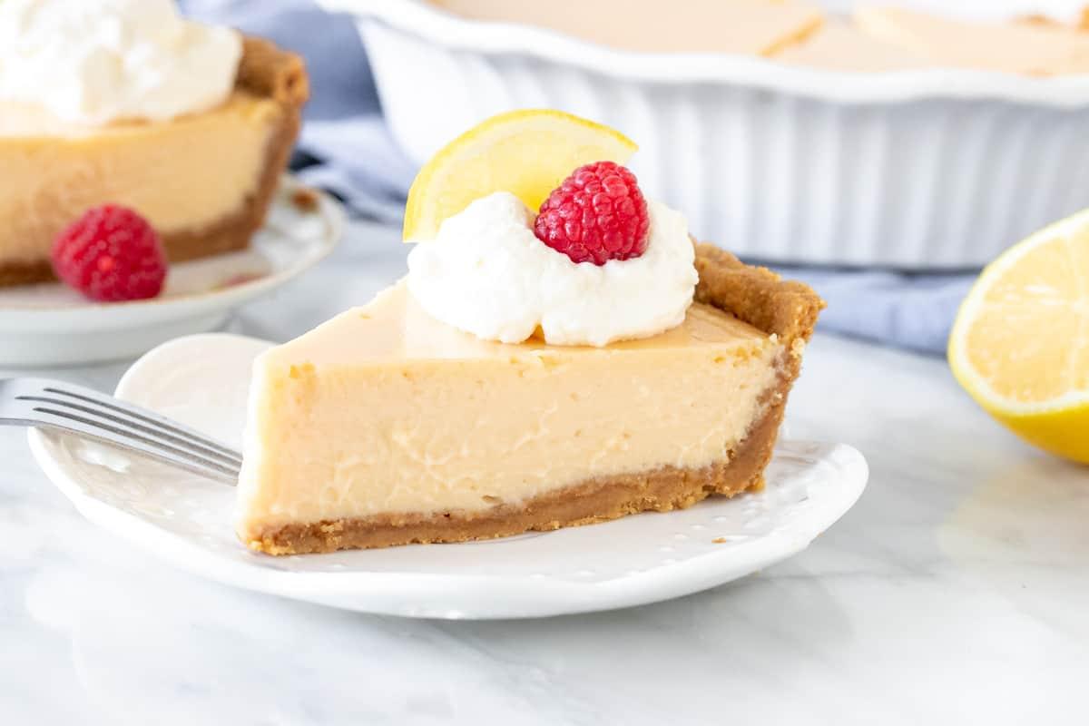 Slice of lemon creamy pie with whipped cream on top