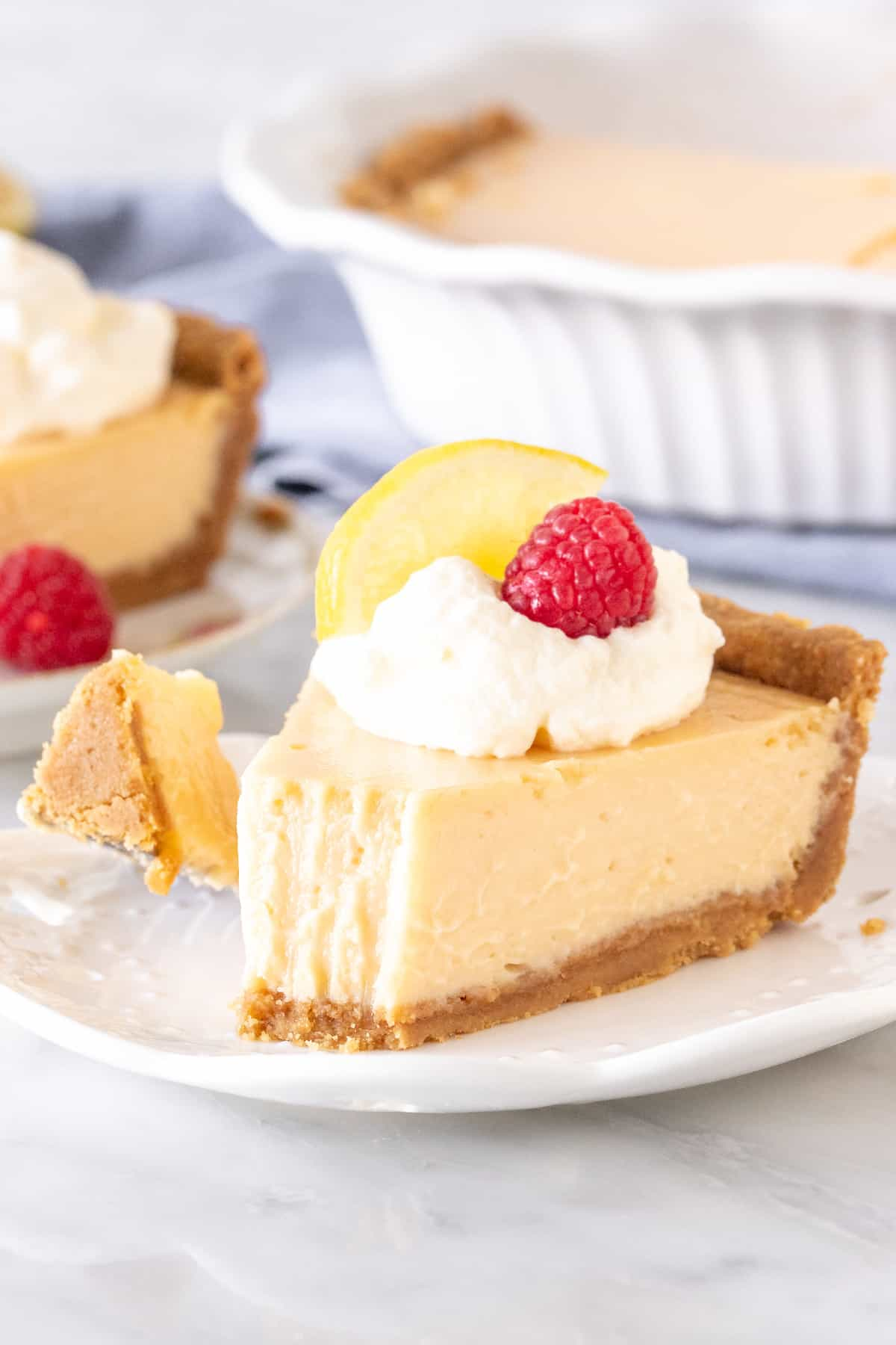 Slice of lemon pie with a graham cracker crust.