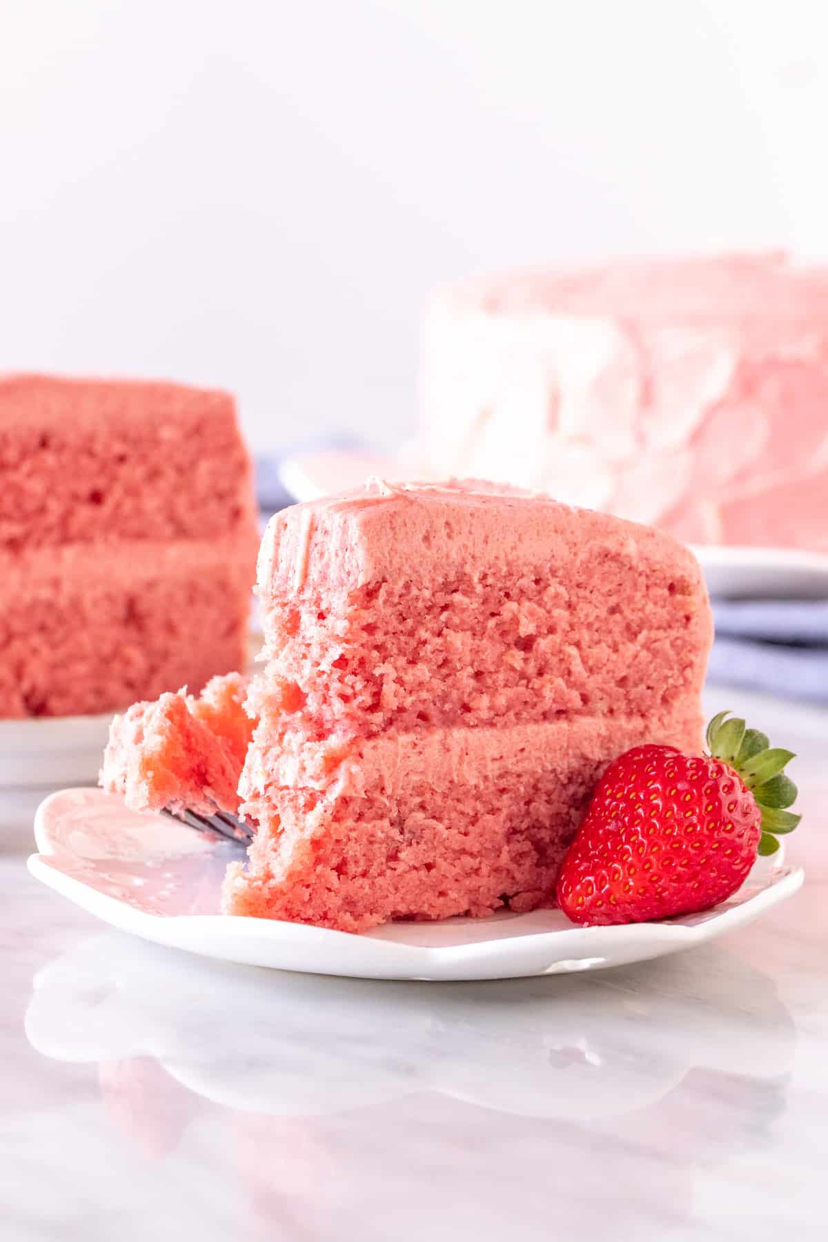 Slice of strawberry cake with strawberry frosting on a plate.