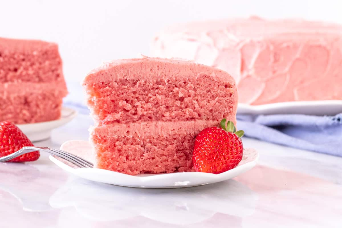 Slice of strawberry flavored cake with strawberry frosting on a plate.