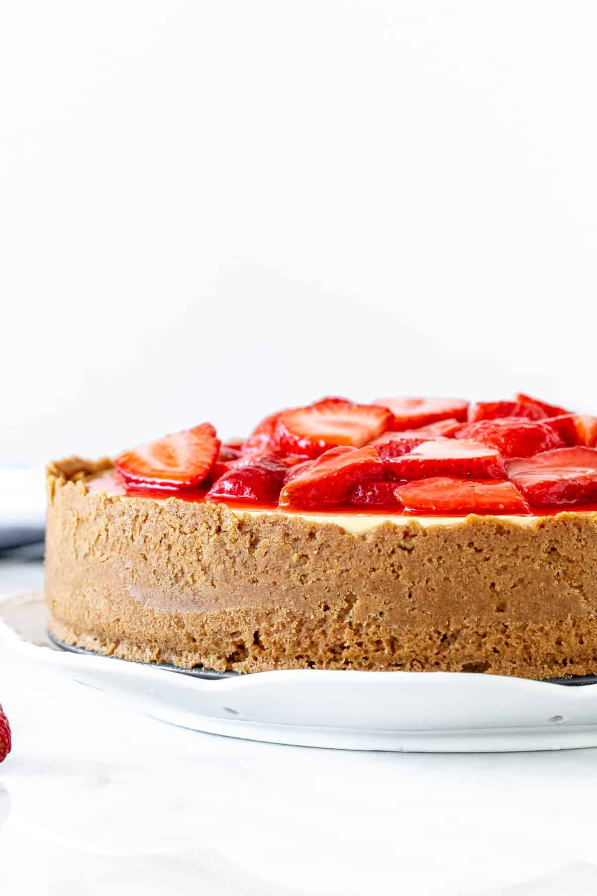 Cheesecake with strawberry topping and a graham crumb crust around the sides.