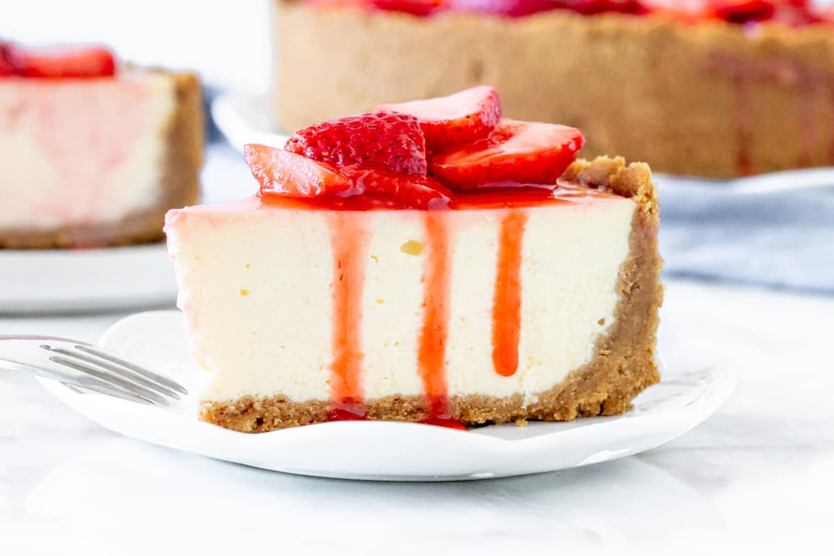 Slice of cheesecake with strawberries on top.