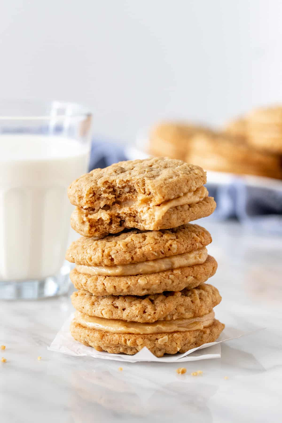 Stack of peanut butter sandwich cookies with glass of milk.