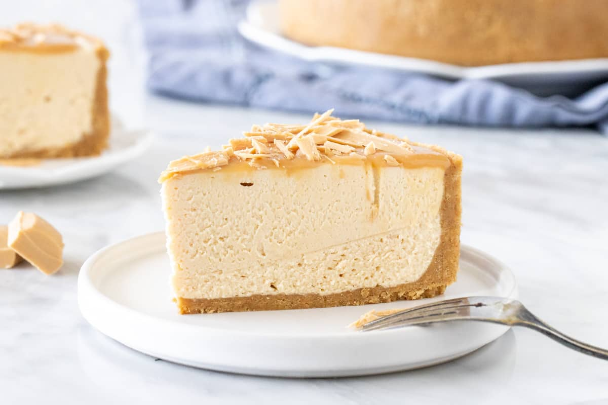 Slice of no-bake caramilk cheesecake with a thick biscuit crust.