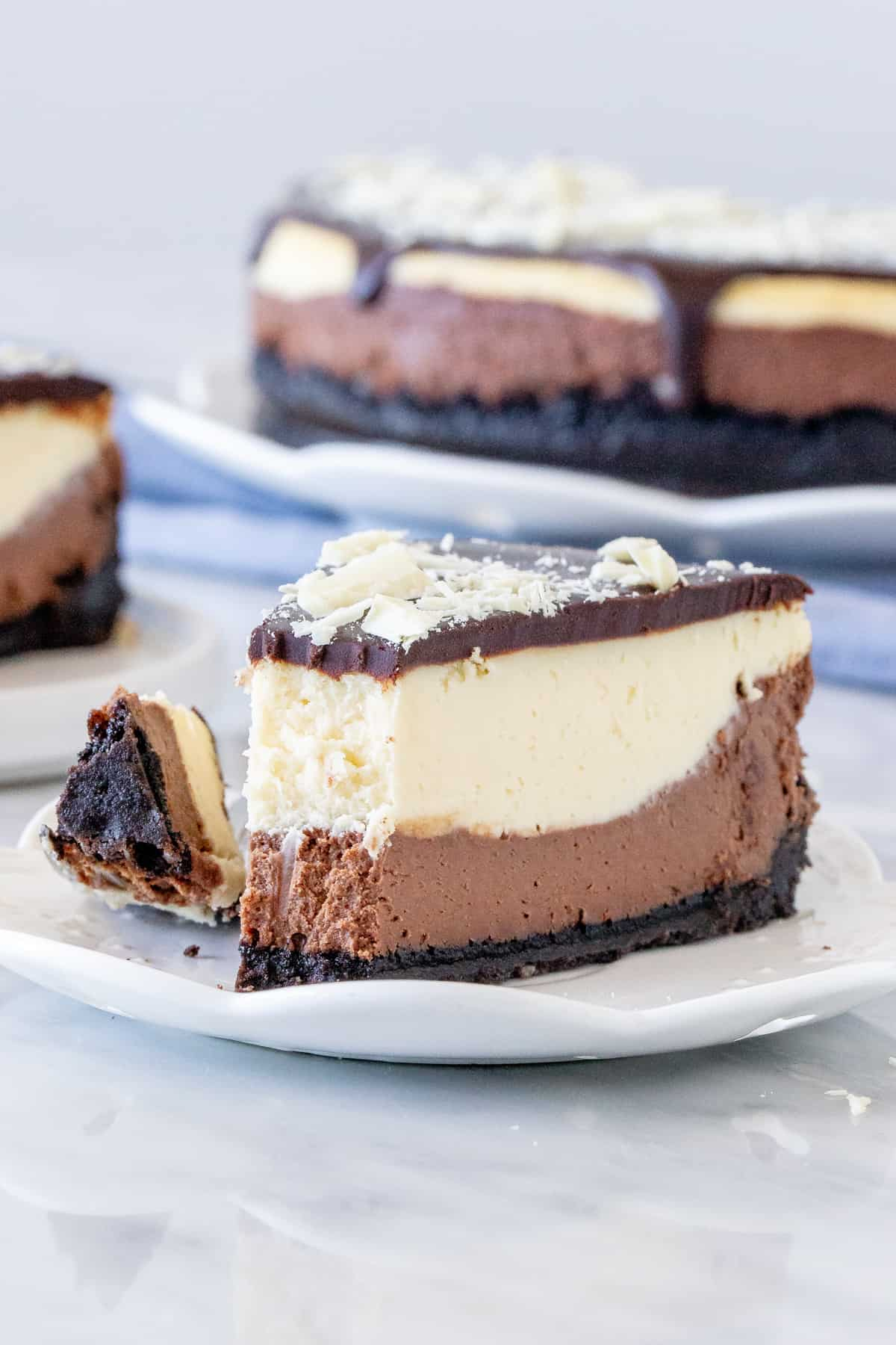 Slice of layered cheesecake with a bite.