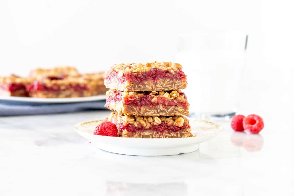 Raspberry bars stacked on a plate.