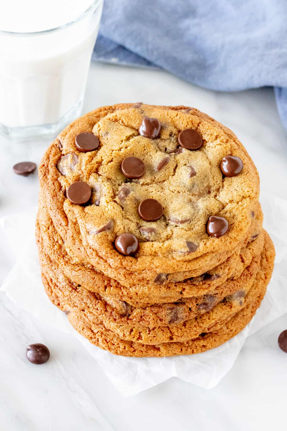 Bakery style chocolate chip cookies stacked one on top of another.