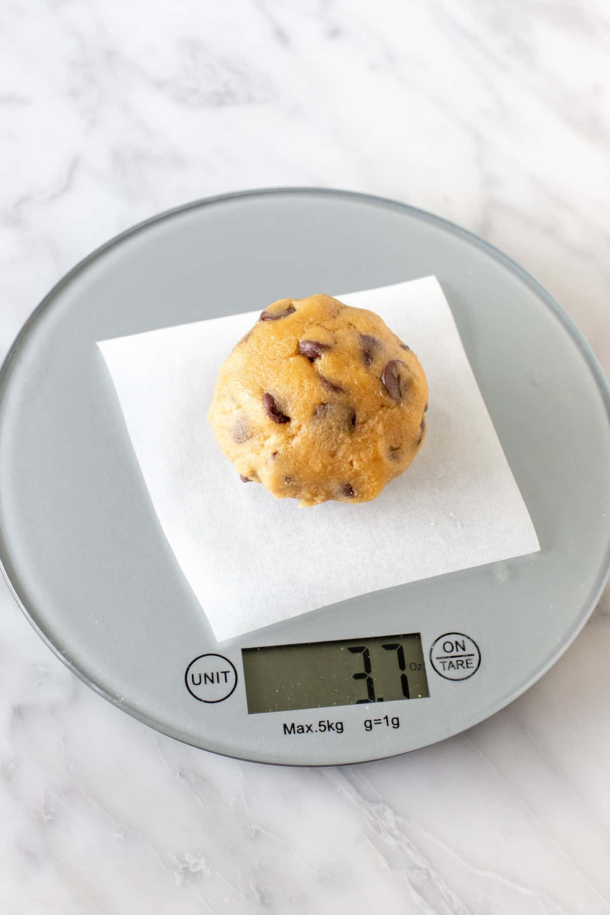 Cookie dough ball on a baking scale.