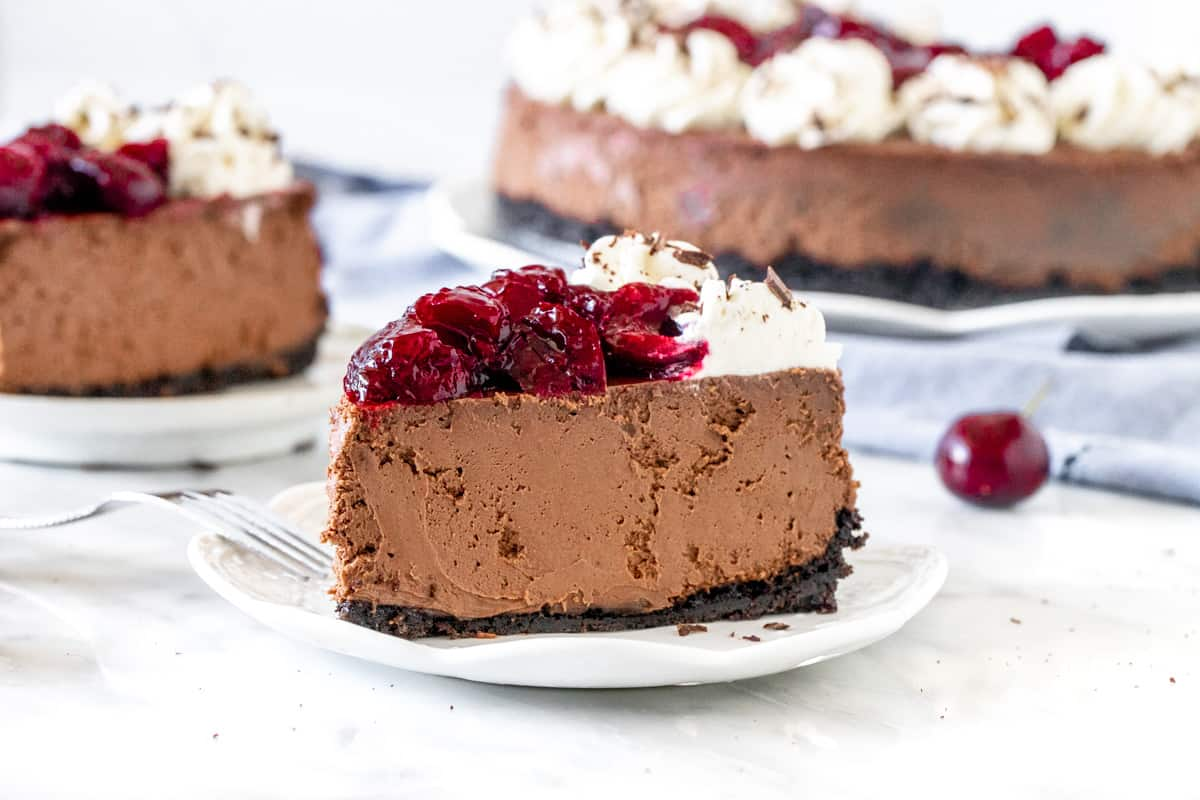 Slice of chocolate cheesecake with cherries on top