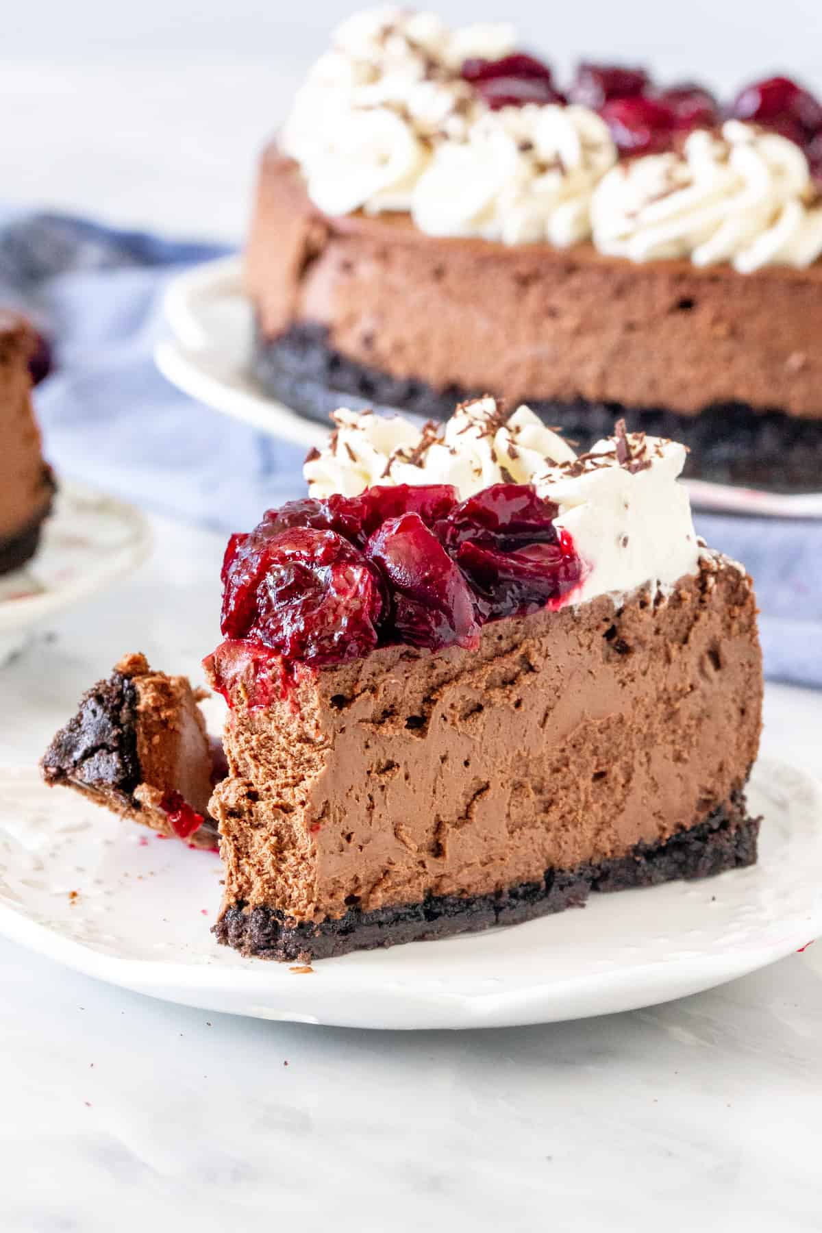 Piece of chocolate cheesecake with cherry sauce on top