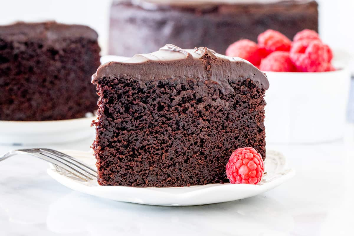 Slice of chocolate cake with a bowl of raspberries