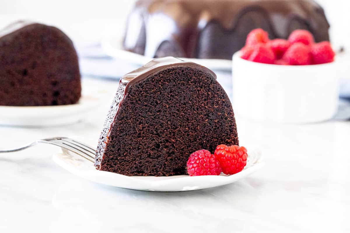 Slice of chocolate bundt cake with a few raspberries.