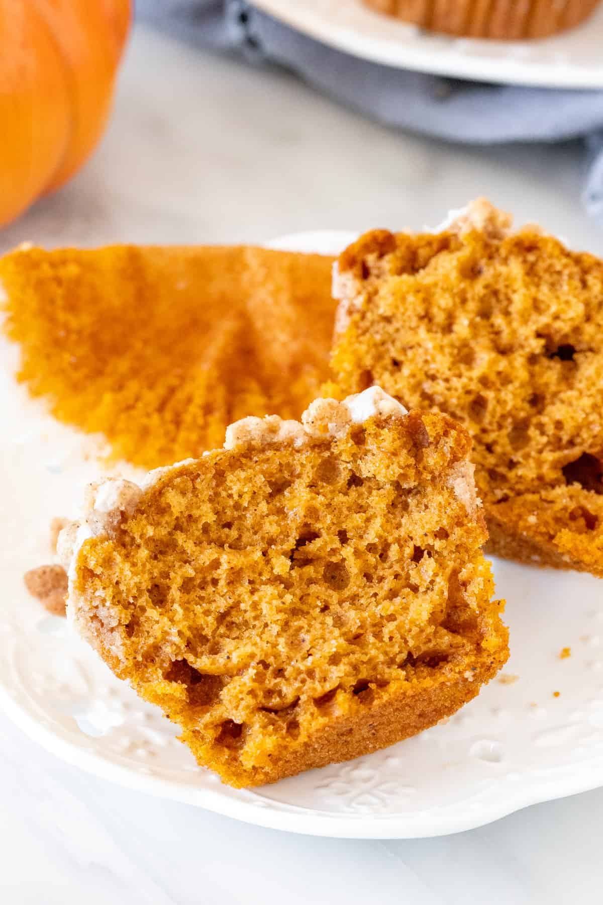 Pumpkin streusel muffin broken in half, on a plate.