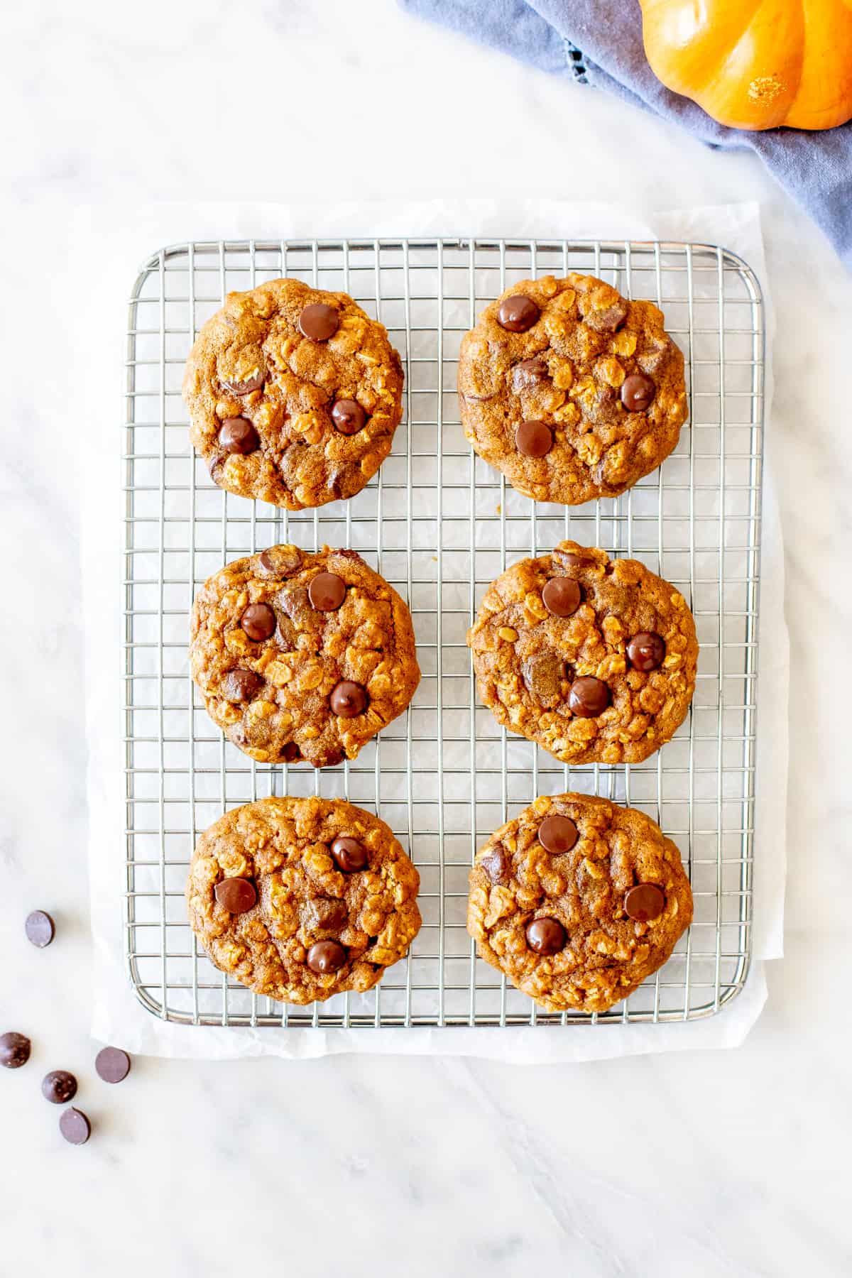 6 pumpkin chocolate chip cookies on a cookie rack.