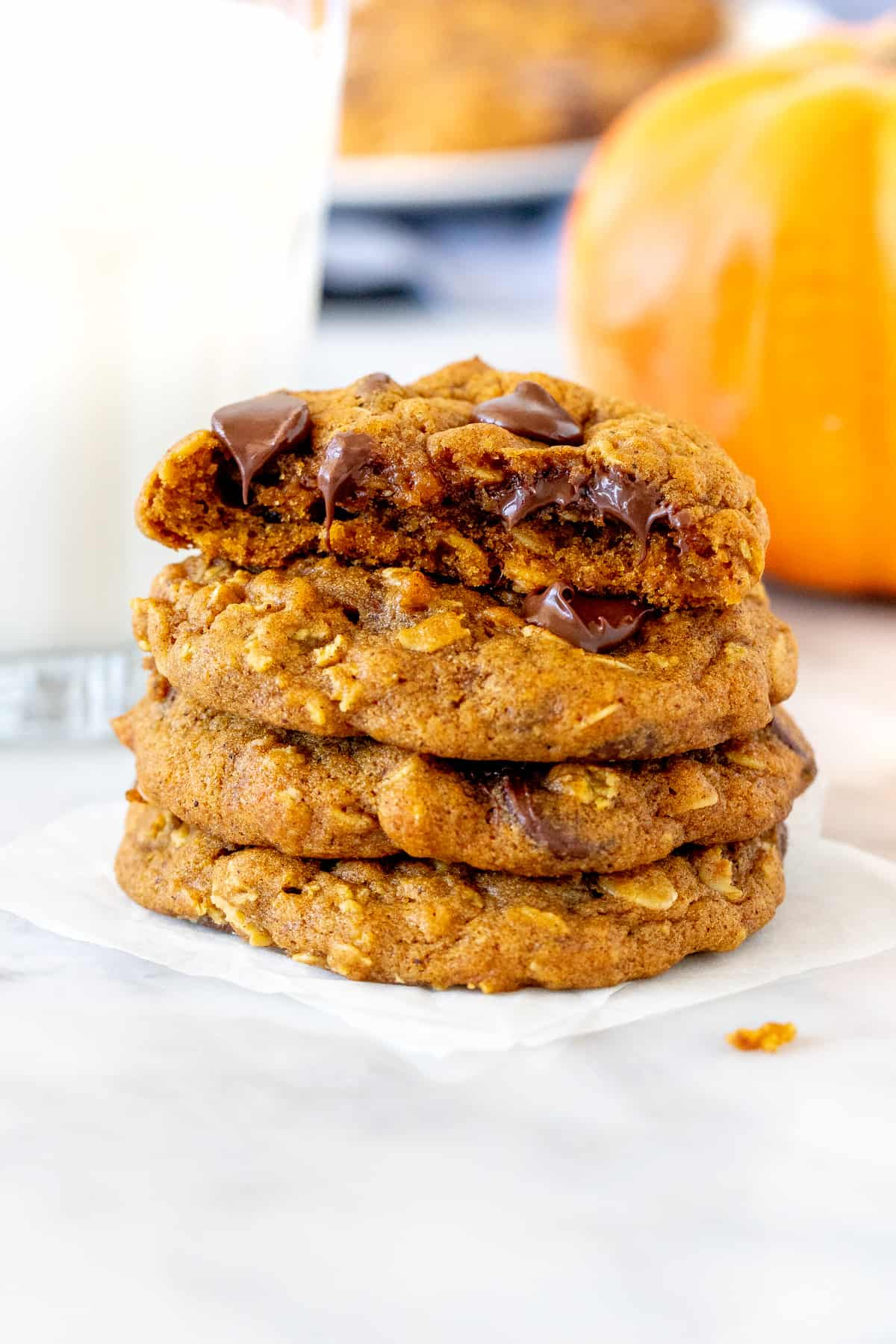Stack of pumpkin chocolate chip oatmeal cookies with a glass of milk.