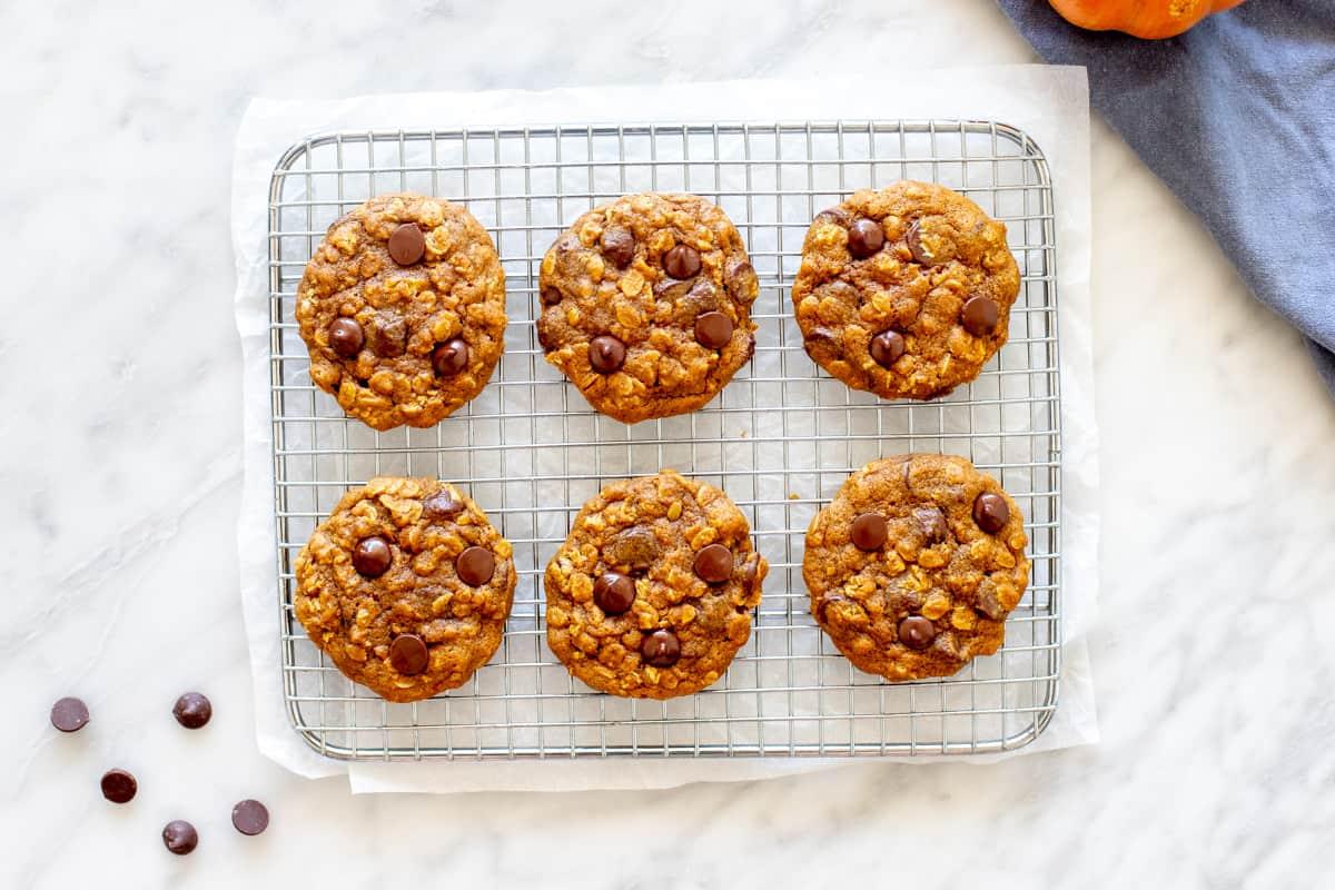 6 pumpkin oatmeal cookies on a cooling rack.