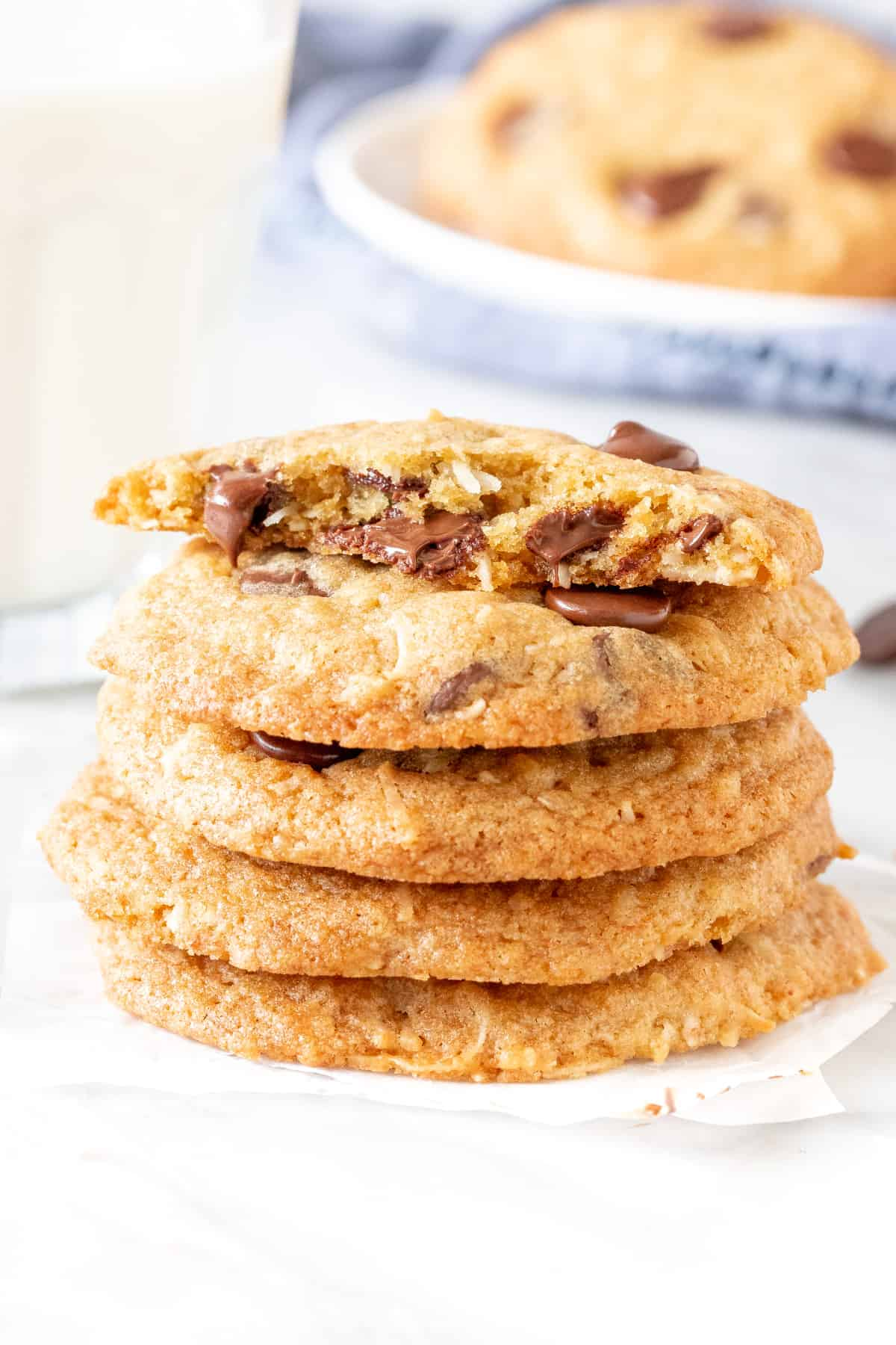 Stack of coconut chocolate chip cookies with a glass of milk