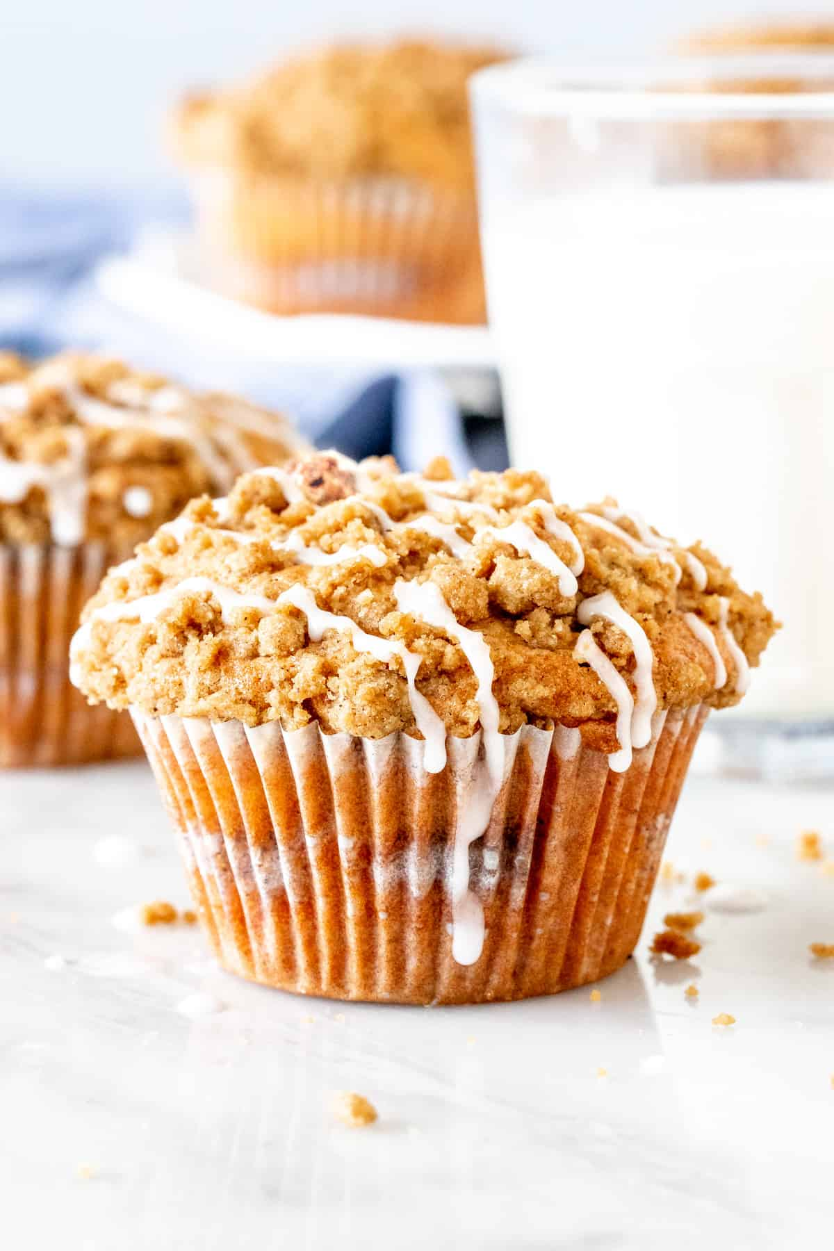 Coffee cake muffin with streusel on top and a drizzle of glaze.