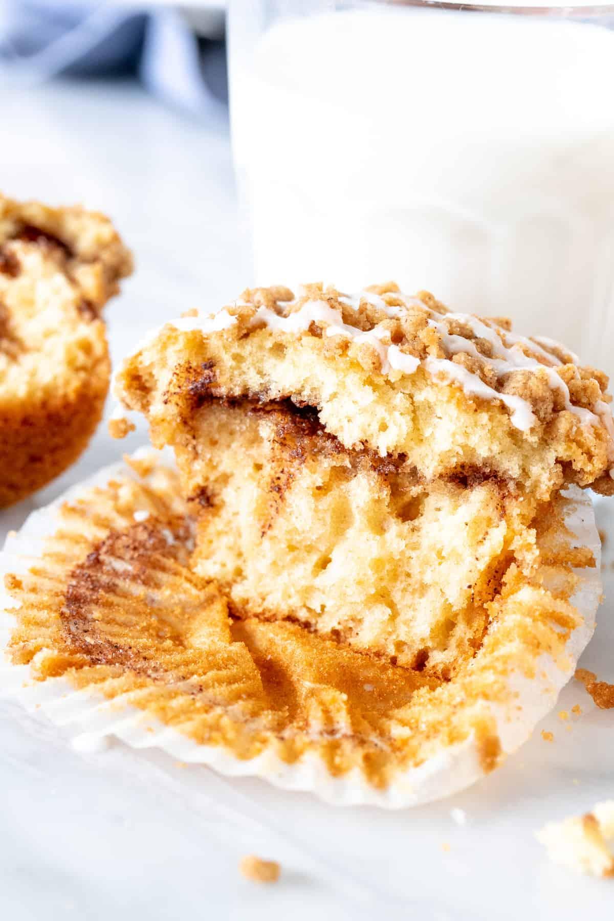 Cinnamon coffee cake muffin, broken in half with a glass of milk.