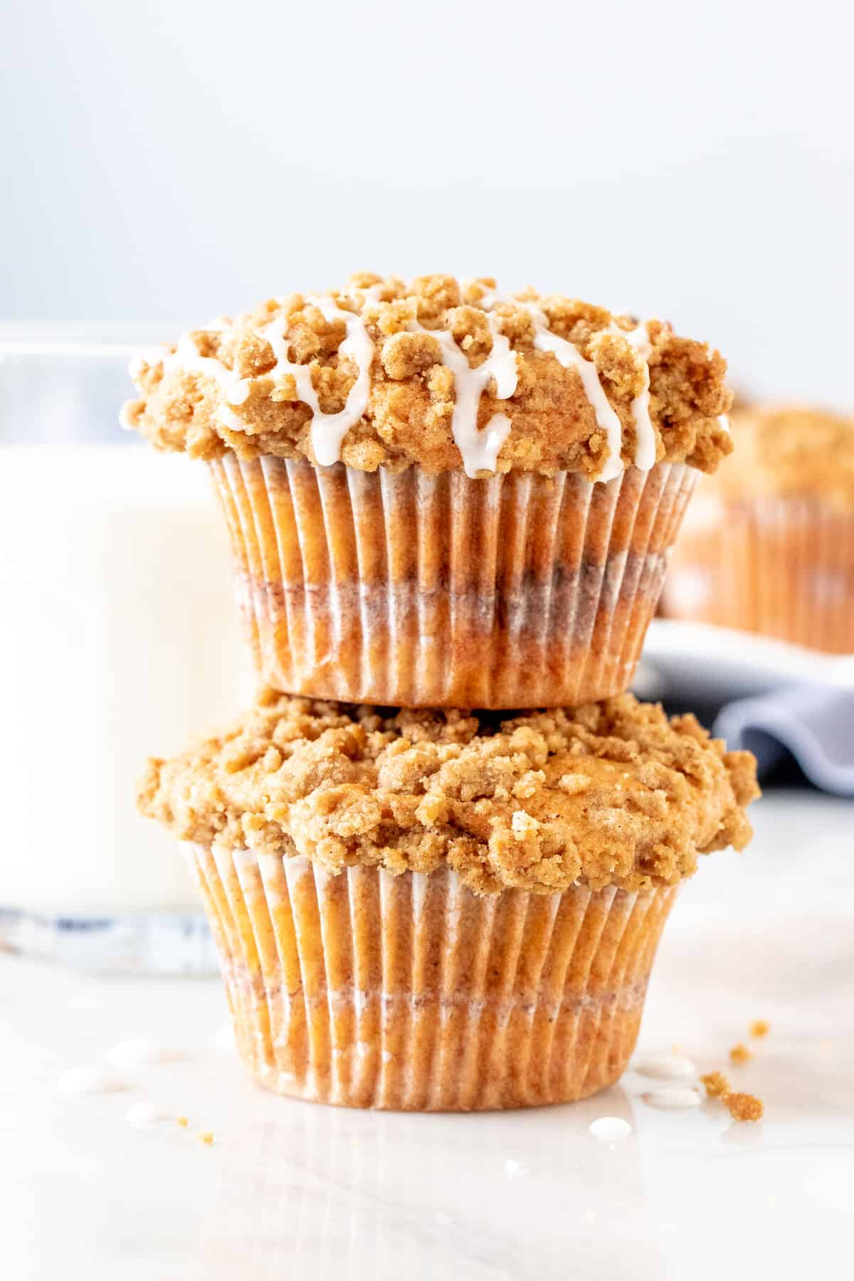 2 crumb cake muffins stacked on top of each other.