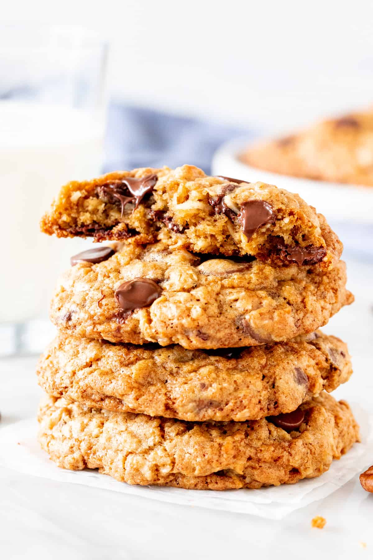 Stack of oatmeal coconut chocolate chip cookies, with the top cookie broken in half
