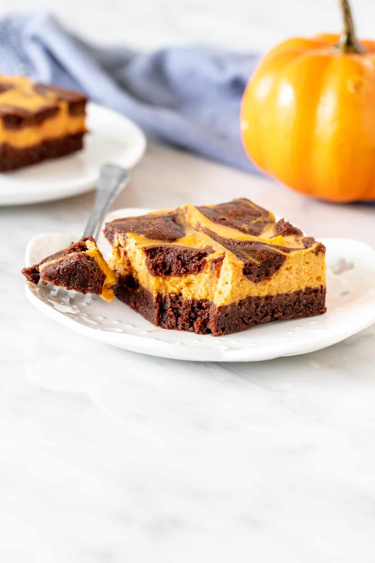 Swirled pumpkin cheesecake brownie on a plate with a bite taken out.