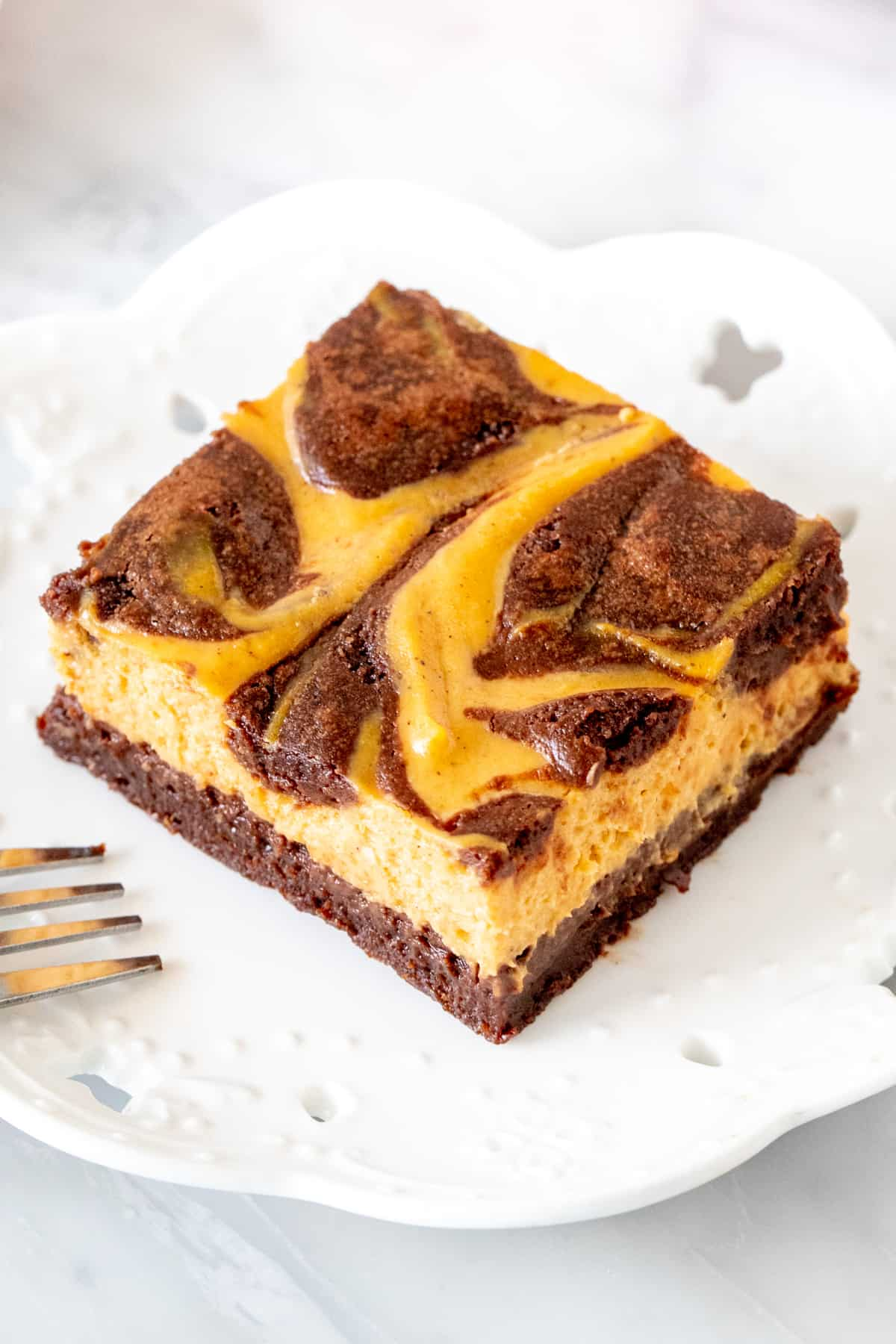 Swirled pumpkin cheesecake brownie on a plate.